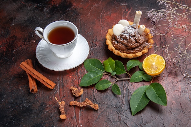 Draufsicht tasse tee mit köstlichem kleinen kuchen auf dunklem tischplätzchen-dessertkeks