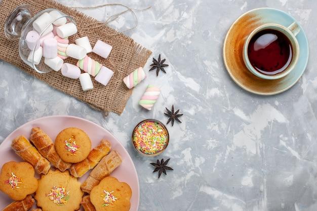 Draufsicht tasse tee mit köstlichen kleinen marshmallows und kuchen auf weißem schreibtisch