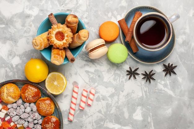 Draufsicht tasse tee mit kuchen und macarons auf weißer oberfläche