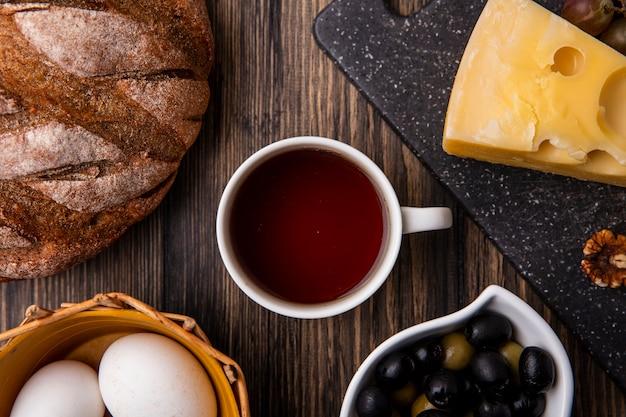 Draufsicht tasse tee mit maasdam-käse auf einem ständer mit oliven und schwarzbrot auf dem tisch