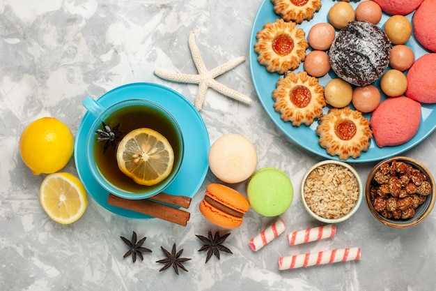 Draufsicht tasse tee mit macarons keksen und kuchen auf der weißen oberfläche