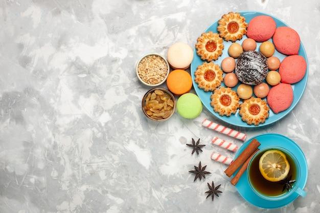 Draufsicht tasse tee mit macarons keksen und kuchen auf weißem schreibtisch