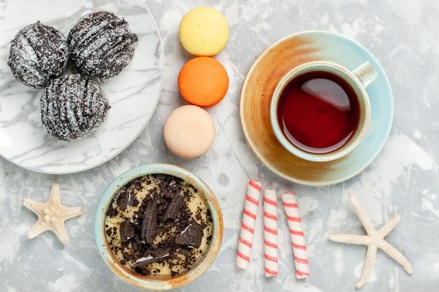 Draufsicht tasse tee mit macarons schokoladenkuchen und bonbons auf weißem schreibtisch backen kuchen kekszucker süße torte