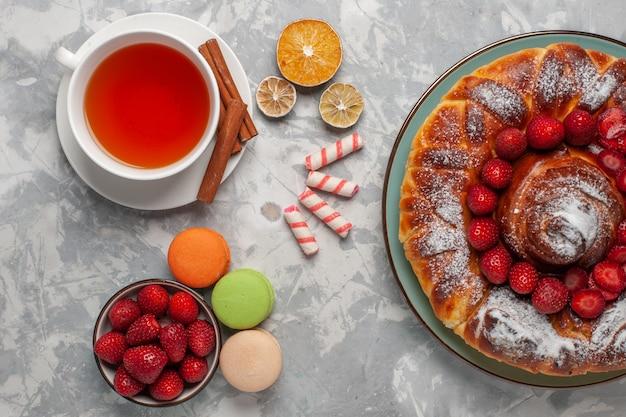 Draufsicht tasse tee mit macarons und erdbeerkuchen auf hellweißer oberfläche