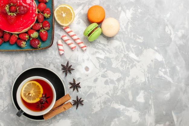Draufsicht tasse tee mit macarons und kleinem erdbeerkuchen auf weißer oberfläche