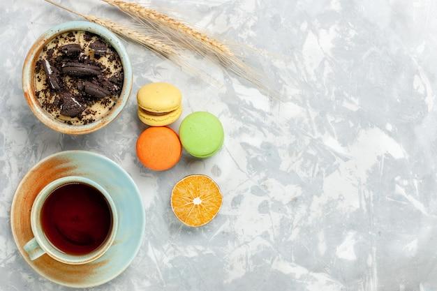 Draufsicht tasse tee mit macarons und schokoladenkeksdessert auf hellweißem schreibtischkeks süß backen zuckerkuchenkeks