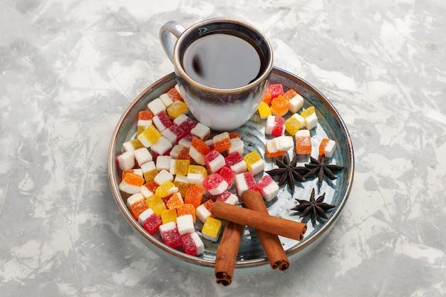 Draufsicht tasse tee mit marmelade und zimt auf hellweißer oberfläche
