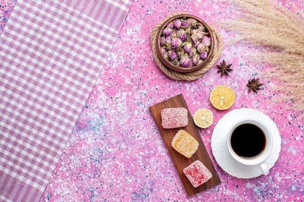 Draufsicht tasse tee mit marmeladenstücken auf rosa schreibtisch.