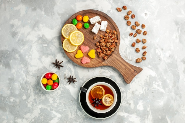 Draufsicht tasse tee mit nüssen und bonbons auf weißem wandbonbon zucker süßer kekskuchen tee