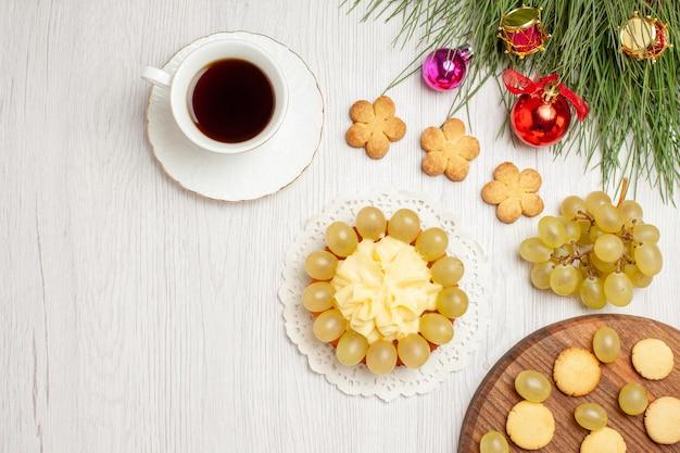 Draufsicht tasse tee mit sahnetorte und trauben auf weißem schreibtisch früchtetee dessert sahne kekskuchen