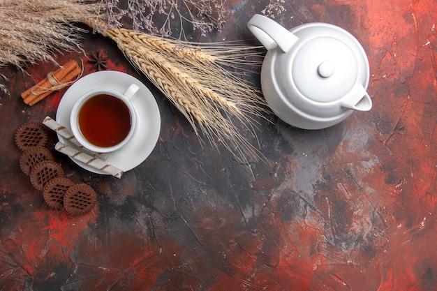 Draufsicht tasse tee mit schoko-keksen auf dunklen tischtee-keks-keksen