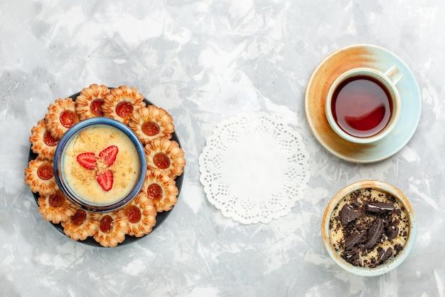 Draufsicht tasse tee mit schokoladenplätzchen-dessert und marmeladenplätzchen auf hellweißem schreibtischplätzchen-schokoladenkuchen backen kuchenzucker süß