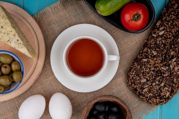 Draufsicht tasse tee mit schwarzbrotkäse gurken und tomaten und oliven mit hühnereiern auf einer beigen serviette