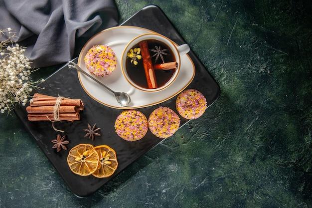 Draufsicht tasse tee mit süßen keksen in teller und tablett auf dunklem hintergrund