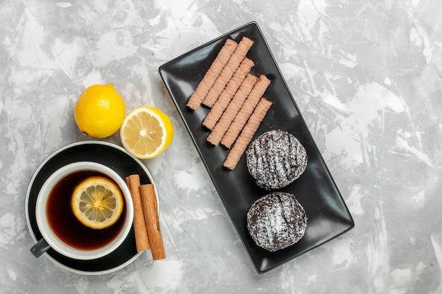 Draufsicht tasse tee mit süßen keksen und schokoladenkuchen auf weißen oberfläche kekse keks süßer zucker kuchen tee
