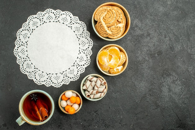 Draufsicht tasse tee mit süßigkeiten und keksen auf grauen tischtee süße kekse