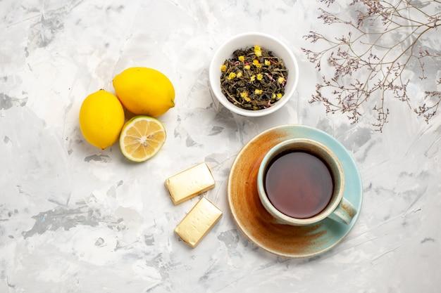 Draufsicht tasse tee mit süßigkeiten und zitrone auf weißem raum