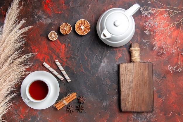 Draufsicht tasse tee mit wasserkocher auf dunklem tisch