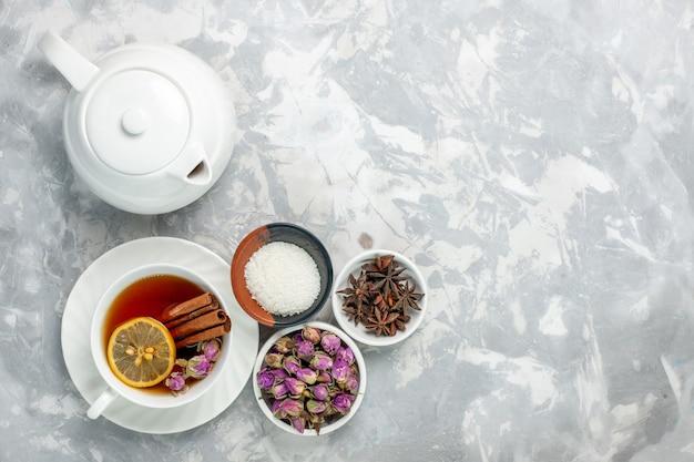 Draufsicht tasse tee mit wasserkocher und blumen auf weißer oberfläche