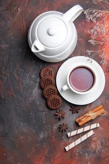 Draufsicht tasse tee mit wasserkocher und keksen auf dem dunklen tisch
