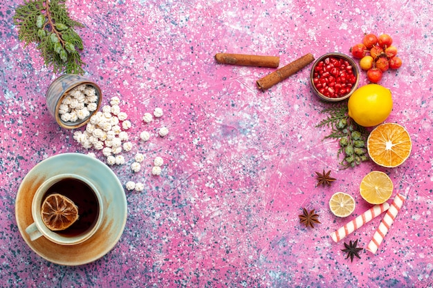 Draufsicht tasse tee mit weißen süßen confitures und zimt auf hellrosa schreibtisch