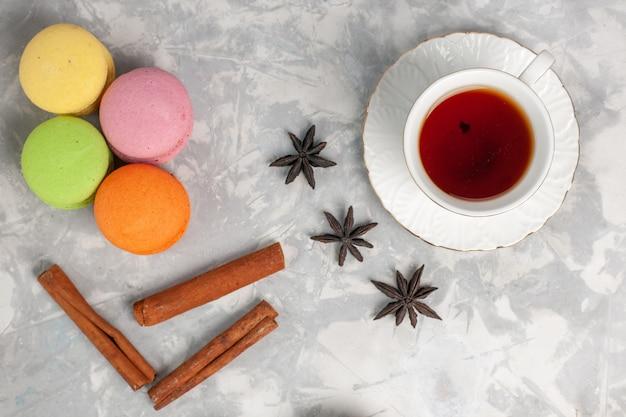 Draufsicht tasse tee mit zimt und französischen macarons auf dem hellweißen schreibtischkuchen backen keks süßer zuckerkeks