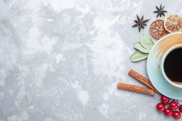 Draufsicht tasse tee mit zimt und getrockneten zitronenscheiben auf weißem schreibtisch tee bonbon farbe frühstücksfrucht