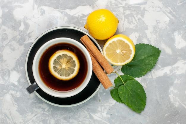 Draufsicht tasse tee mit zimt und zitrone auf der hellweißen oberfläche