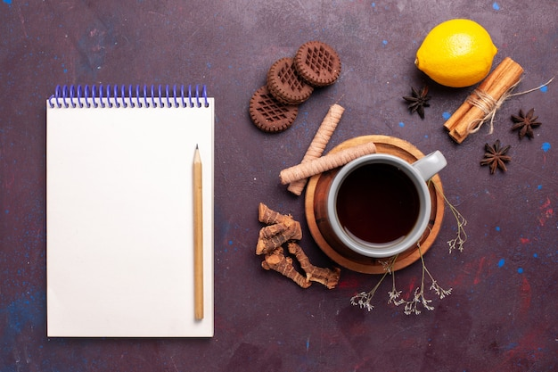 Draufsicht tasse tee mit zimtplätzchen und zitrone auf dunklem hintergrund tee süßes farbfoto