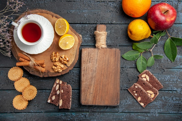 Draufsicht tasse tee mit zitrone und süßigkeiten auf dem dunklen tisch