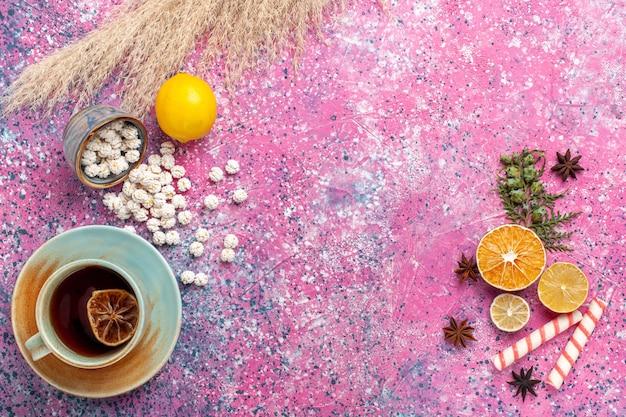 Draufsicht tasse tee mit zitrone und weißen süßen confitures auf rosa oberfläche