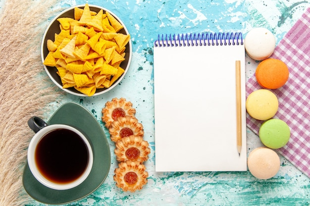 Draufsicht tasse tee mit zuckerplätzchen macarons und chips auf hellblauem hintergrundplätzchenkekszucker süßer teekuchenkuchen
