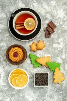 Draufsicht tasse teeschalen mit schokoladen- und zitronenscheiben weihnachtsplätzchen auf grauer oberfläche