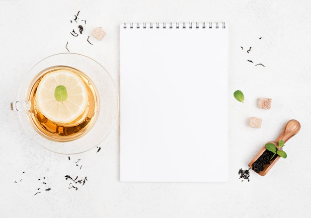 Draufsicht tee mit zitrone mit notizbuch