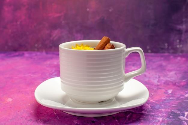 Draufsicht teetasse mit kräutern und zimt auf rosa