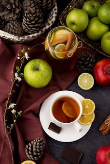 Draufsicht teetasse tee mit zitrone und zimt eistee mit limette zitronen zimt dunkle schokoladengrüne rote äpfel weiße blumen und tannenzapfen