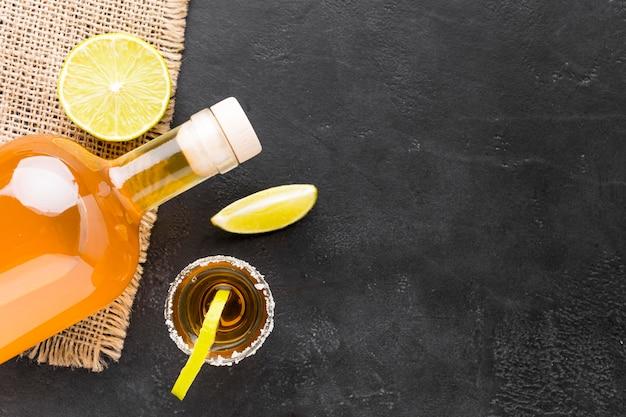 Draufsicht tequila-aufnahmen mit limettenscheiben und flasche mit kopierraum