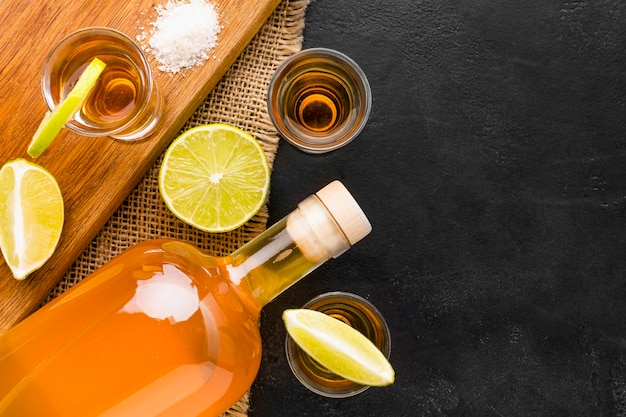 Draufsicht tequila-aufnahmen und limettenscheiben auf schneidebrett mit kopierraum