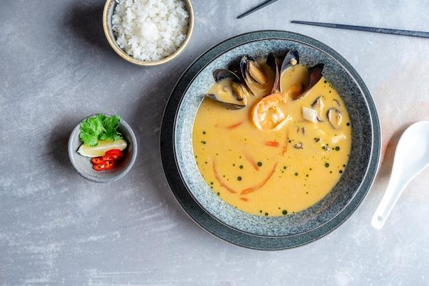 Draufsicht tom yam mit meeresfrüchten serviert mit reisschüssel und zitrone