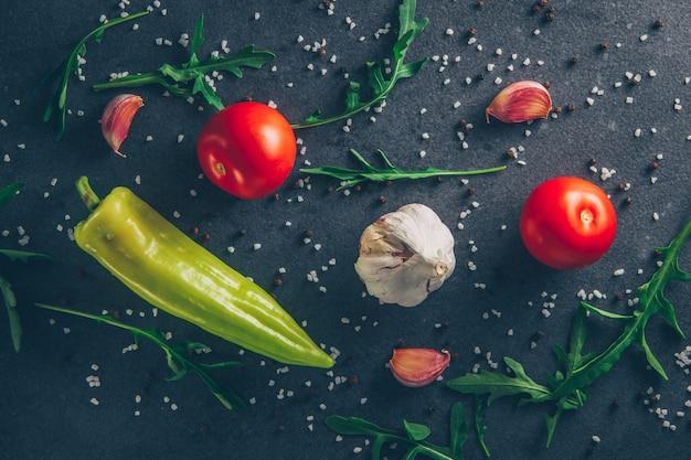 Draufsicht-tomaten mit knoblauch, grün und pfeffer auf grauem strukturiertem hintergrund. horizontal