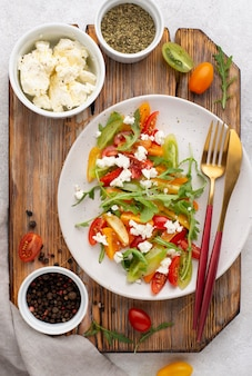 Draufsicht tomatenmischsalat mit feta-käse, rucola und schwarzem pfeffer