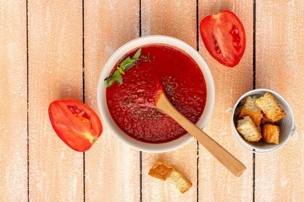Draufsicht tomatensuppe mit gemüse zusammen mit roten tomaten auf rustikalem tisch, suppenessen mahlzeit abendessen gemüse