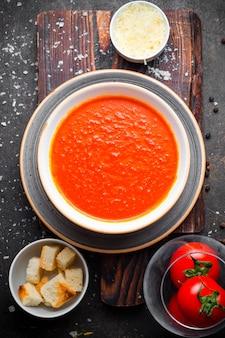 Draufsicht tomatensuppe mit tomaten und crackern und käse im teller