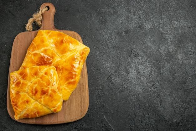 Draufsicht torten an bord zwei appetitliche torten auf dem schneidebrett auf der linken seite des tisches