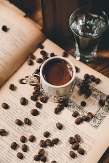 Draufsicht traditioneller türkischer kaffee mit kaffeebohnen auf einem offenen buch mit einem glas wasser