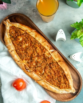 Draufsicht traditionelles türkisches gericht fleischpide auf einem tablett mit tomaten und saft