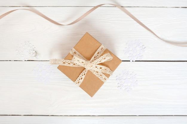 Draufsicht über das nette eingewickelte weihnachtsgeschenk, weihnachtsbaumdekorationen