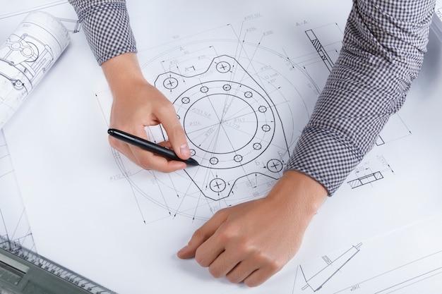 Draufsicht über die mannhände, die auf dem papier mit mechanischem liegen