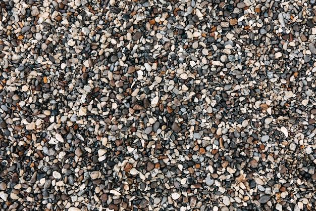 Draufsicht über einen grauen und braunen kieselstein am strand