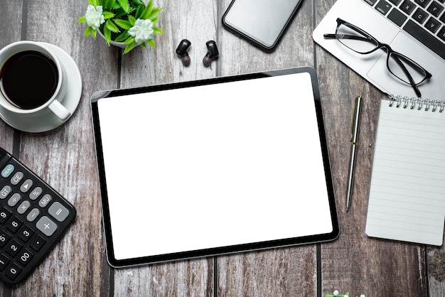 Draufsicht über holztisch mit leerem weißem bildschirm der tablette und briefpapier.